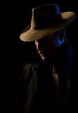 Villain - chiaroscuro film noir lighting. Hoodlum/gangster - or possibly private eye - with ominous lighting, looking out under his hat brim.  Looks good in Stock Images