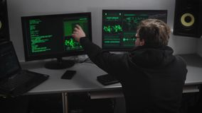 Villain hacker analyzes illegally obtained data on the monitor screens for creating spy software. Young man in a glasses stock footage
