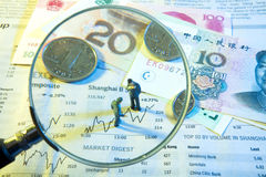 Villain with a magnifying glass dolls and coins Stock Images