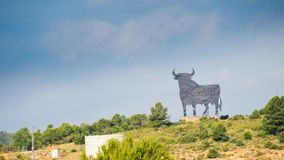 Toro Osborne, iconic symbol of Spain, silhouette of black bull on the hill with green bush at the foreground royalty free stock photo