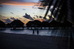 Villas with silhouetted honeymooners, Maldives Stock Photography