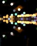 Ville brouillée la nuit, fond de bokeh Taches jaunes et vertes sur le noir Photographie stock