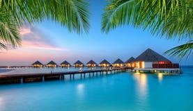 Ville dell'acqua sull'isola di vacanze delle Maldive nel tramonto Fotografia Stock
