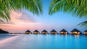 Ville dell'acqua sull'isola di vacanze delle Maldive nel tramonto Immagine Stock