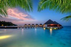 Ville dell'acqua sull'isola di vacanze delle Maldive nel tramonto Fotografie Stock Libere da Diritti