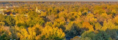 Ville des arbres dans la pleine couleur d'automne avec une église Photographie stock