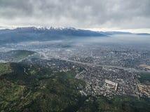 Ville entre le jour nuageux de montagnes photographie stock libre de droits