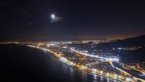 Ville gentille la nuit avec la lune Photos libres de droits