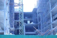 Ville moderne construisant en construction avec des grues et le TR vert Photo libre de droits