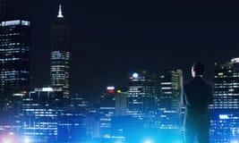 Ville rougeoyante de nuit de visionnement d'homme d'affaires photos libres de droits
