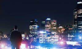Ville rougeoyante de nuit de visionnement d'homme d'affaires image stock