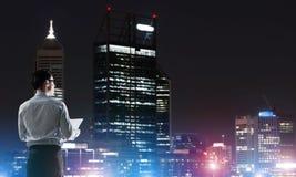 Ville rougeoyante de nuit de visionnement d'homme d'affaires photo stock