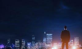Ville rougeoyante de nuit de visionnement d'homme d'affaires images stock