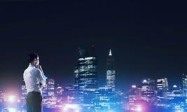 Ville rougeoyante de nuit de visionnement d'homme d'affaires photo libre de droits