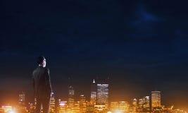 Ville rougeoyante de nuit de visionnement d'homme d'affaires photographie stock libre de droits