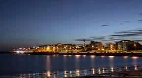 Ville sur la banque de l'océan la nuit Image stock