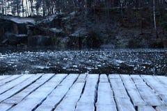 Villebrådlandskap Träbräden i frost på den djupfrysta sjön i sten bryter sten i vinter Djupfryst sjö med is och träbron Arkivbild