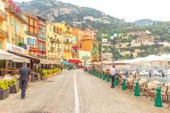 Villefranche-sur-Mer - Cote d'Azur, Франция 24-ое июня 2018: взгляд гавани и людей взморья на террасах улицы в красочном городке  стоковые изображения