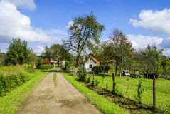 Villgae scene. Tranquil village scenery - gravel road through field and garden Royalty Free Stock Images