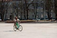 VILNA, LITUANIA - 10 DE ABRIL DE 2012: Rider Riding en la bicicleta en la ciudad vieja de Vilna fotos de archivo libres de regalías