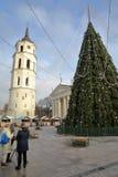 VILNA, LITUANIA - 28 DE DICIEMBRE DE 2016: Mujeres que tienen una bebida delante de un árbol de navidad en cuadrado de la catedra Fotografía de archivo