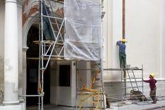 Vilnius Litauen - Juni 20, 2016: Byggnadsarbetare i material till byggnadsställningåterställande av den gamla byggnaden i Oldtown Royaltyfri Fotografi