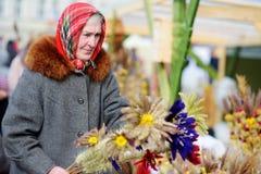 VILNIUS, LITAUEN - 4. MÄRZ 2016: Ältere Frau, die traditionelle handgemachte Litauer-Ostern-Palme bekannt als verbos verkauft Stockfotos