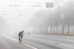 VILNIUS LITAUEN - 21 OKTOBER, 2018: Cyklist som passerar den tomma gatan på dimmig morgon royaltyfri foto
