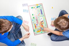 Vilnius, Lithuania - 23 April 2017: Children playing board game Monopoly royalty free stock image