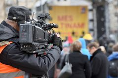 TV camera man filming a political event. Vilnius, Lithuania - April 15, 2018: TV camera man filming a political event in Vilnius on April 15, 2018. Vilnius is Royalty Free Stock Image