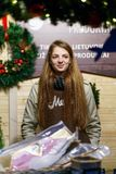 Smiling girl selling Christmas wreathes at Christmas Market in Vilnius. Vilnius, Lithuania - December 4, 2016: Smiling girl selling Christmas wreathes and meat Royalty Free Stock Photos