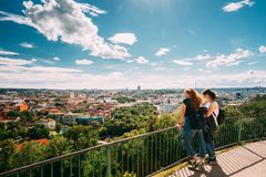 Vilnius, Lithuania Duas jovens mulheres que olham a vista da cidade velha de Vilnius da plataforma da visão perto de três cruzes Imagens de Stock Royalty Free