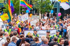 Pride parade in action. Crowd of watchers and demonstrators with rainbow flags. Event celebrating lesbian, gay, bisexual,. Vilnius, Lithuania - July 27, 2013 stock image