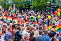 Pride parade in action. Crowd of watchers and demonstrators with rainbow flags. Event celebrating lesbian, gay, bisexual,. Vilnius, Lithuania - July 27, 2013 royalty free stock photo