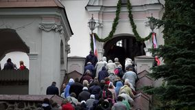 Catholic people on stairs to church entrance