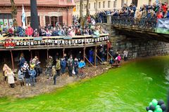 VILNIUS, LITHUANIA - MARCH 18, 2017: Hundreds of people enjoying festivities and celebrating St. Patrick`s day in Vilnius. Vilnele river was dyed green to mark Stock Photos