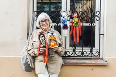 Senior lady selling handmade knitted toys on the street stock images