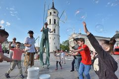 Street artist makes big soap bubbles. Vilnius, Lithuania, May 4: Unknown street artist makes big soap bubbles in a public square on May 4, 2018 in Vilnius Royalty Free Stock Images