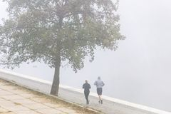 VILNIUS, LITHUANIA - 21 OCTOBER, 2018: Couple runners going for jog in morning fog by riverside. royalty free stock images