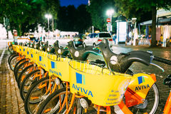 Vilnius Lithuania. Row Of Bicycles Aviva For Rent At Lit Bike Parking Stock Photos