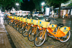 Vilnius Lithuania. Row Of Bicycles Aviva For Rent At Lit Bike Parking On Wet Cobblestone Of Pilies Street Stock Photography
