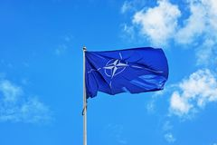Vilnius, Lithuania - September 3, 2015: Flag of NATO waving in the wind. In front of blue sky and white clouds stock photos