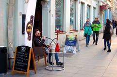 Vilnius; Lithuania, 04/30/2017,Street life: man Smoking hookah in Vilnius, Lithuania. Street life: man Smoking hookah Stock Photo