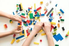 Vilnius, Lithuanie - avril 2017 Les mains d'enfants jouent avec les blocs colorés de lego sur la table blanche photos stock
