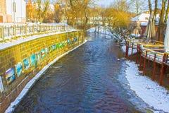 VIlnius, Litouwen - Januari 05, 2017: Vilnelerivier die voorbij Uzupis-district, een buurt in Vilnius, Litouwen stromen stock foto's