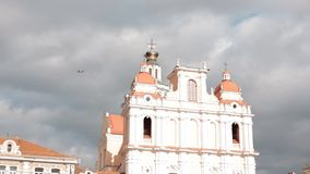 Vilnius, Litouwen Vliegtuig die boven Kerk van St Casimir vliegen Bestemming toneel De oude Stad is Unesco-Werelderfenis stock video