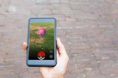 Vilnius, Lituânia - 24 de julho de 2016: A pessoa que guarda o telefone celular e que joga Pokemon vai - lugar-baseado aumentado Fotografia de Stock