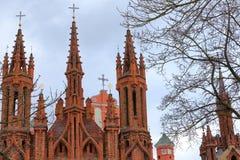 VILNIUS, LITUÂNIA: Os pináculos da igreja e da Bernardine Church do ` s de St Anne no fundo imagens de stock