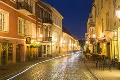 Vilnius Lituânia Vista da rua abandonada de Pilies na iluminação de noite brilhante imagem de stock royalty free