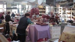 Vilnius, Lituania Il venditore della donna nel mercato di Halle vende la salsiccia ed altri prodotti a base di carne Il venditore stock footage